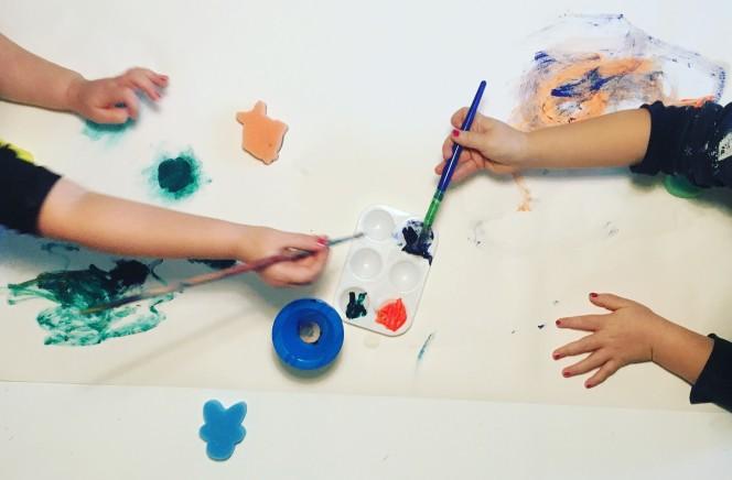 Barn målar liggande
